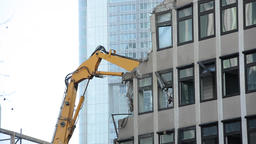 High Reach Demolition Excavator Working Behind Building Facade Remnants Live Action