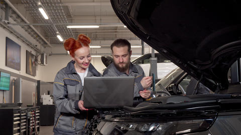 Professional auto mechanics using laptop during car diagnostic at the garage Footage