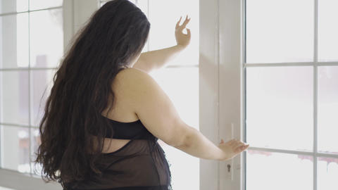 Portrait of attractive young plus size girl looking in the window close-up. Back Footage