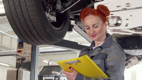 Female car mechanic examining wheels of a car on a lift, taking notes on Footage