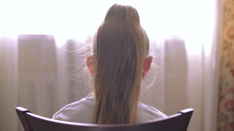 Young blond girl with hair tail sitting on chair front window in home room. Girl Live Action