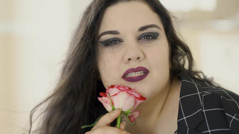 Close-up portrait of adorable overweight woman sniffing rose indoors. The hair Live Action