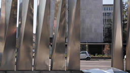 City Buildings and Car Traffic Through Metal Sculpture Pillars Footage