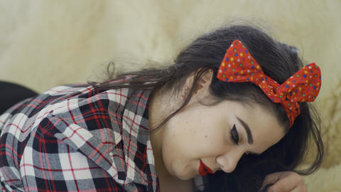 Pretty overweight girl with bright make-up lying on the sofa posing looking in Footage