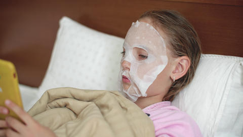 Young girl with cloth cosmetics mask on skin face lying on bad. Teenager girl Footage
