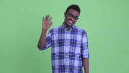 Happy young African hipster man with eyeglasses waving hand Footage
