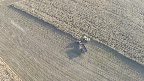 Farm machinery busy with crop harvesting, aerial view Footage