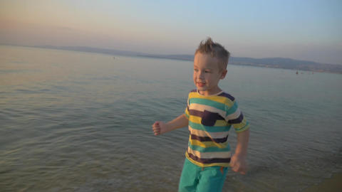 Happy boy running on the sea coast at sunset Footage