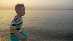 Smiling Boy Running along the Sea Footage