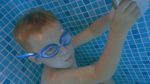 Boy in Goggles Holding Breath in Swimming Pool Footage