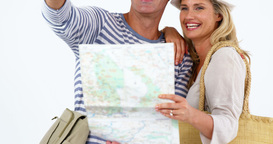 Smiling couple looking at map and pointing against white background Live Action