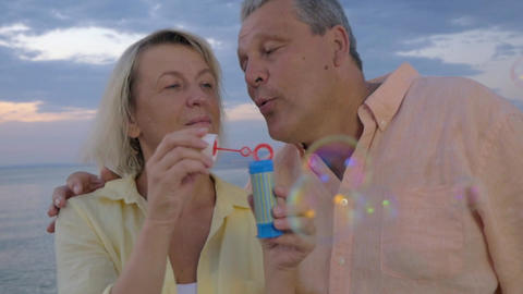 Senior couple blowing bubbles at the seaside Footage