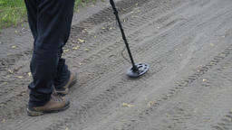 Treasure hunter on road with electronic metal detector, scanning ground road Footage
