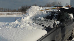Woman is removing snow from a car. Winter. Slow Motion Footage