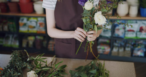 Young woman florist arranging beautiful flowers making composition in shop Footage