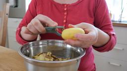 Woman is preparing dinner. Potatoes peeling Footage