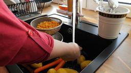 Woman is rinsing dry peas on a sieve. Dinner preparation Footage