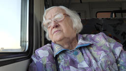 Old woman looks through the window in a train Footage