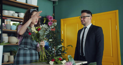 Friendly florist arranging flowers and talking to businessman customer in shop Footage
