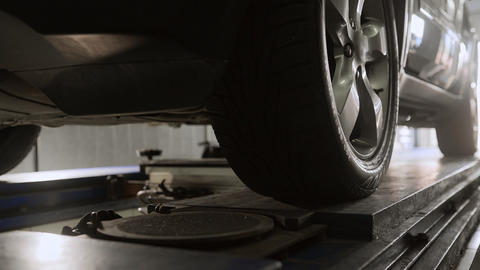 Mechanic moves and prepares car on the service stand for wheel alignment, car Footage