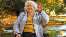 Portrait of senior woman waving into camera Footage