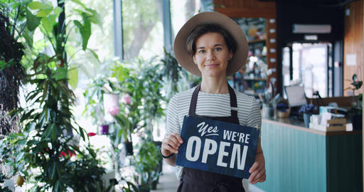 Portrait of flower shop owner holding we are open sign standing in workplace Live Action