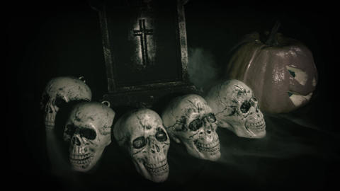 Old film look of halloween set decoration with skulls, grave and jack o'lantern Live Action