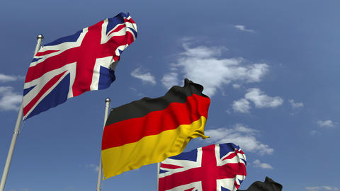 Waving flags of Britain and Germany on sky background, loopable 3D animation Live Action