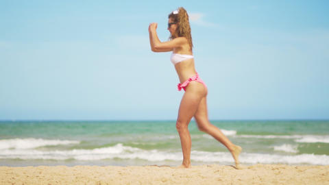 A girl in a bathing suit plays sports against the backdrop of the sea. Effective Footage