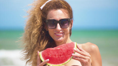 Smiling woman eating watermelon on beach. Woman eating tasty summer fruit. Happy Live Action