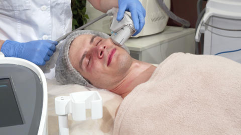 Handsome man getting rejuvenating procedure at cosmetology clinic Live Action