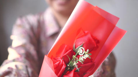 Asian lady with smile gives a bouquet of one red rose to you. for love one. Valentine's day. Slow Footage