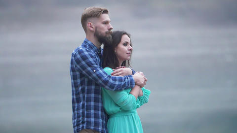 Loving couple is hugging by standing near lake shore Smooth motion frame Live Action