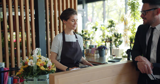 Businessman purchasing basket of flowers paying with card talking to cashier Live Action
