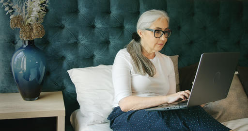 Elderly Woman Indoors with Laptop Live Action