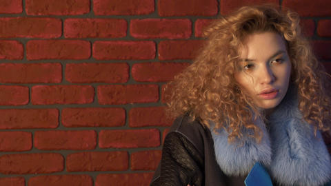 Curly haired young woman posing in front of brick wall Footage