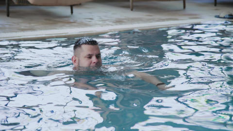 Young man swims in the indoor pool Footage