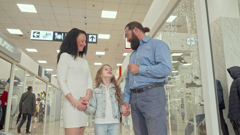 Mature couple and their cute daughter enjoying shopping spree at the mall Footage