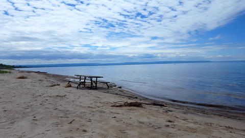 Picnic Table Along Beautiful Sand Beach Shore. Daytime Sunny Vacation Shoreline Beach Destination in Live Action