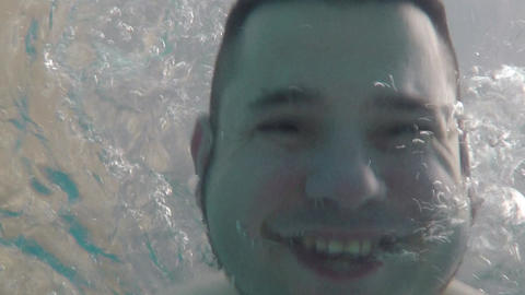 Cheerful funny man swims in the pool. Action camera at the bottom of the pool Live Action