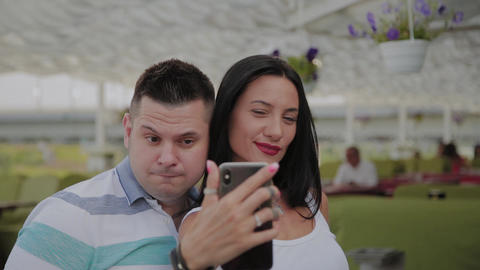 A beautiful woman and a cheerful man take a selfie on the veranda of the Footage