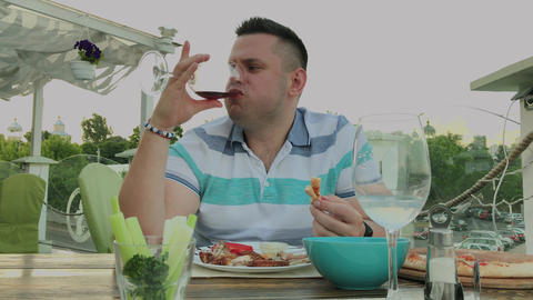 A man eagerly eats junk food in a restaurant Live Action
