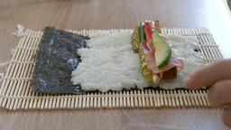 Preparing homemade vegan sushi with avocado, smoked tempeh, red paper and pickle Footage