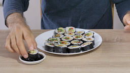 Man is eating sushi with wasabi paste and soy sauce Footage