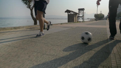 Two Men Dribbling Soccer Ball on the Footwalk ビデオ