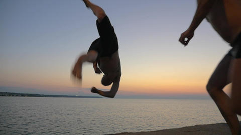 Two young guys doing tricks jumping from pier Footage