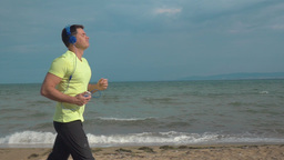 Man Jogging on the Beach with Smartphone Footage