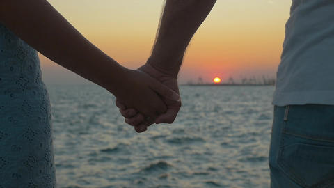 Hand in Hand by the Sea at Sunset Footage