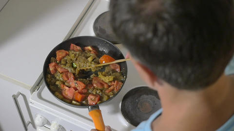 Man stewing tomatoes, mushrooms and potatoes in pan Footage