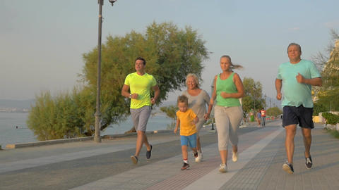 Big family running on road next to the sea Footage